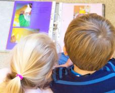 zwei Kinder schauen sich einen Ordner an