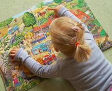 Kind schaut sich ein Bilderbuch an