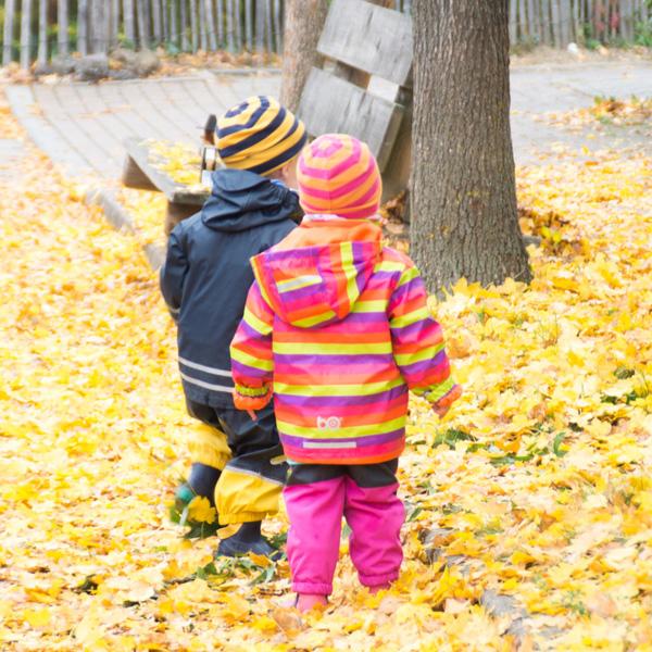 zwei Kinder spazieren durch Herbstlaub